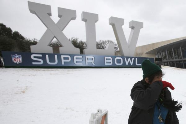 An Australian football fan is blown by a gust of wind after posing for photos in front of Cowboys Stadium in Arlington, Texas. In town for Sunday's Super Bowl, she says this is the first time she has experienced snow.