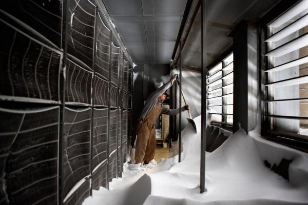 University of Iowa pipefitter Jeff Harland uses a shovel to dig out snow that had blown into the Carver Biomedical Research Building's air supply intake Wednesday in Iowa City, Iowa.