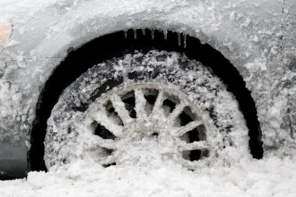 Icicles, snow and slush cover the wheel area of a parked vehicle in Newark, N.J.