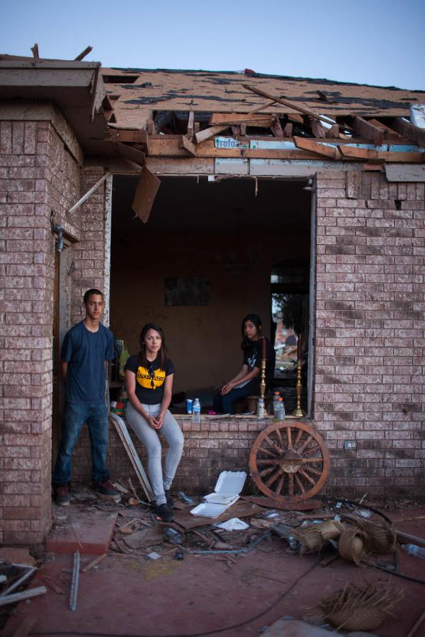Siblings (from left) Alan, Sylvia and Ariel Trillo share a home in Heatherwood — one of few in the subdivision that is still standing, though everything inside is damaged. Sylvia was amazed at the outpouring of help the community received from strangers.