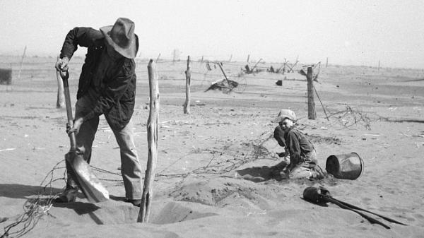 A Dust Bowl farmer digs out a fence post to keep it from being buried under drifting sand in Cimarron County, Okla., in 1936.