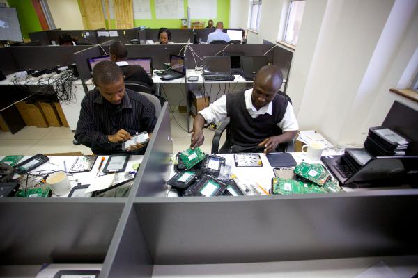 Workers at Bridge's headquarters prepare tablets for use in the school chain's classrooms.