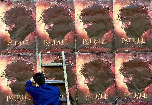 A worker adjusts posters promoting Mel Gibson's <em>The Passion of the Christ</em> in Bucharest, Romania, in April 2004. Worldwide, the film brought in more than $600 million in box-office earnings.