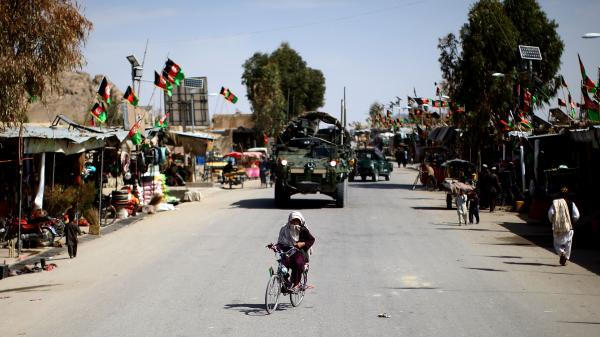 A boy on his bike, with a U.S. Stryker following behind, in the Panjwai district center in southern Afghanistan. For years, this area was one of the most dangerous places in Afghanistan. But it is now considered safe as Afghans prepare to vote in a presidential election Saturday.