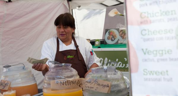 Alicia Villanueva hands change to a customer at a weekly San Francisco street-food market called Off the Grid, where she has a booth selling tamales.