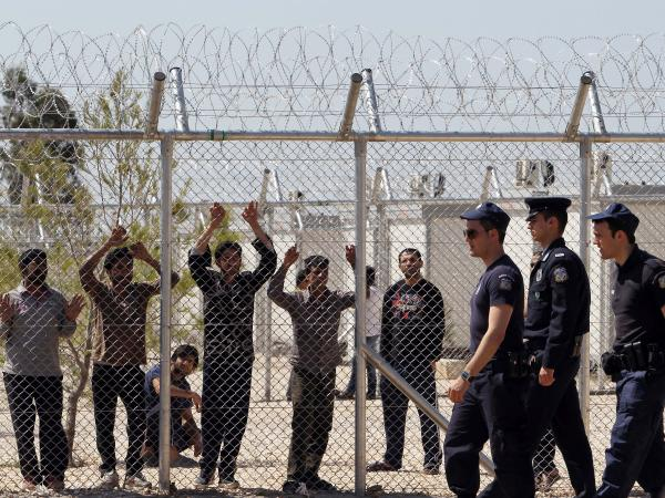 Illegal immigrants watch from behind a fence as police patrol the perimeter of a detention center at Amygdaleza, on the northern fringes of Athens, on April 30, 2012.