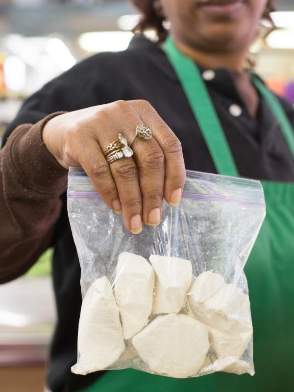 "Vendor Alice Mangham holds a bag of kaolin, or ""white dirt,"" at Sweet Auburn Market in Atlanta."