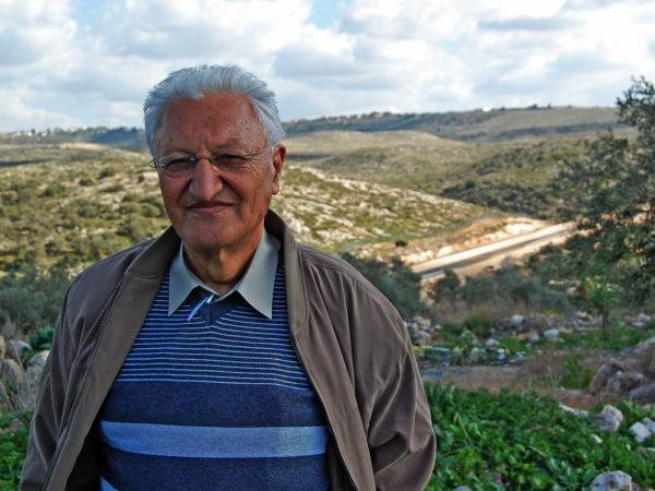 Palestinian-Israeli Hussein Jbara stands near the wall running between his Arab town in Israel and a nearby West Bank village where some of his relatives live.