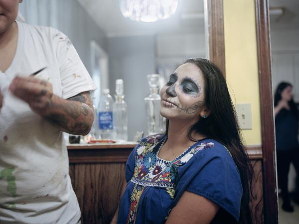 Anai Saucedo has her face painted with makeup in the Dia de los Muertos tradition in Erwin, Tenn.