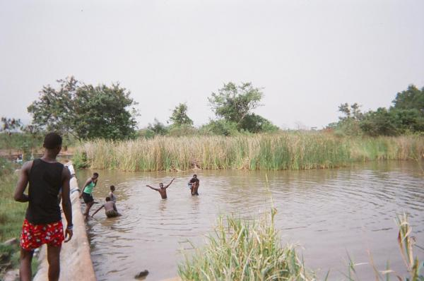 Teenagers spend the day swimming in the dam.