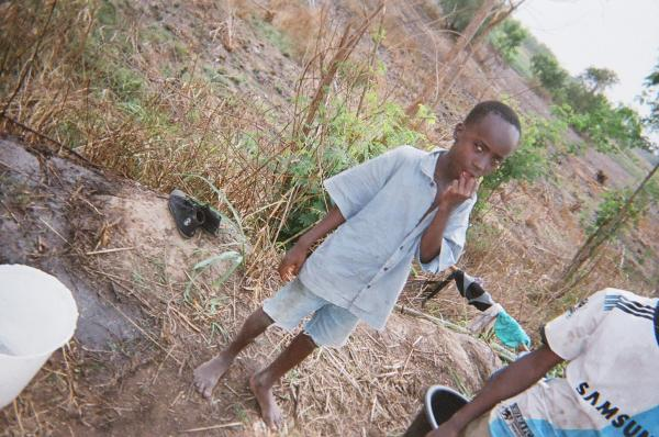 Small boys in Kordiabe walk the long, narrow dirt road to the dam to collect water. Many have fallen sick after drinking the water.
