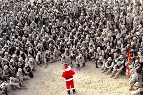 Hundreds of U.S. Marines gather at Camp Commando in Kuwait during a visit by Santa Claus on Christmas Eve, 2002.
