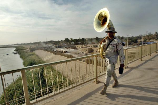 A band member with the U.S. Army 1st Armored Division walks across Baghdad's 14th July Bridge in October 2003.