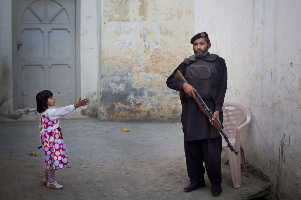 A girl reaches out to greet a Pakistani policeman securing the road outside Kainat Riaz's home in Mingora, Swat Valley, Pakistan, in 2012. Security stepped up after Kainat was wounded by the same Taliban gunman who shot Malala Yousufzai and 13-year-old Shazia Ramazan on Oct. 8 on their way home from school.