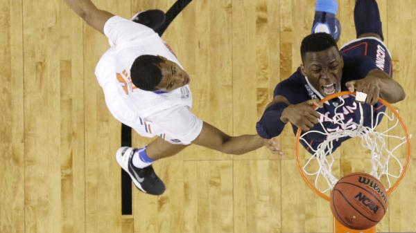 Connecticut center Amida Brimah (right) dunks the ball in front of Florida guard Kasey Hill during the second half of an NCAA Final Four tournament college basketball semifinal game on Saturday. UConn won 63-53.