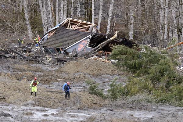 Searchers walk near a demolished house in Oso, Wash., in March. Few homeowners in Washington and neighboring Oregon have mudslide insurance.