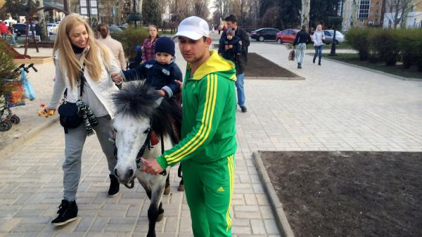 "Emir Gushinov (in green) says not many children are taking his pony rides in Donetsk nowadays. But he said that's not because of the unrest nearby. ""The main reason is that it's not a holiday,"" he says."