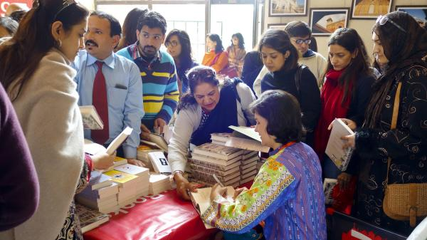 Novelist Kamila Shamsie signs autographs after the Pakistani launch of her latest novel, <em>A God In Every Stone.</em>