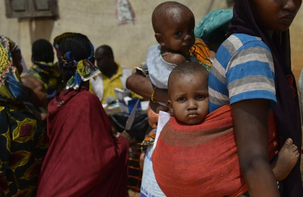 A woman of the Pulaar ethnicity carries a baby on her back as she waits in line in the Begoua district, northeast of Bangui, to receive humanitarian and medical aid on April 9, 2014. (Miguel Medina/AFP/Getty Images)