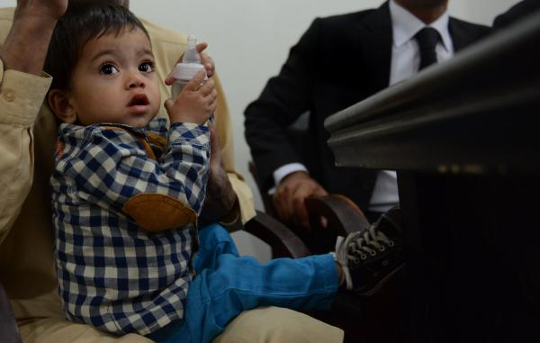 Pakistani toddler Mohammad Musa, seen here sitting in his grandfather Muhammad Yasin's lap after a court hearing in Lahore. A court threw out charges of attempted murder against the toddler Saturday.