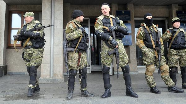 Armed men in military fatigues stood guard Monday outside a regional administration building they seized in the eastern Ukrainian city of Slovyansk.