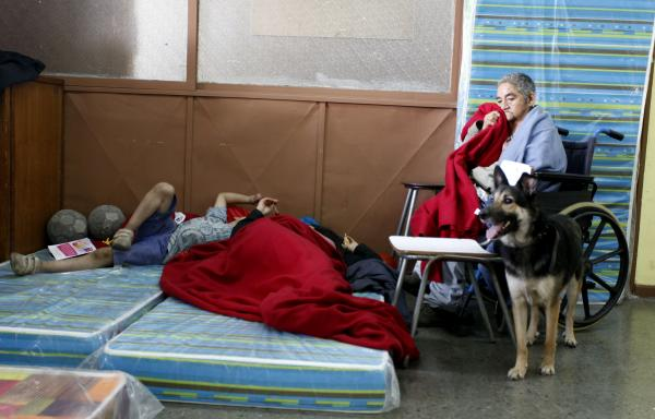 Residents gather in a shelter Sunday after a forest fire burned several neighborhoods in the hills of Valparaiso, northwest of Santiago.