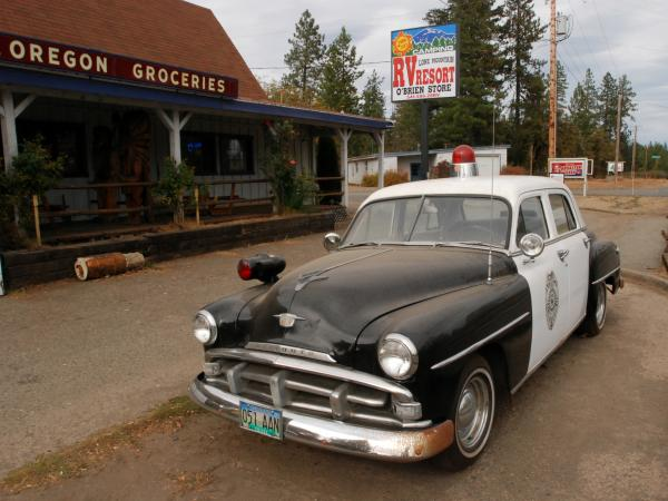 An old police car is permanently parked on the highway through O'Brien, Ore., where cuts to the sheriff's office have prompted some locals to mount crime patrols.