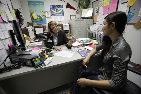 """In this Thursday, May 26, 2011 photo, high school guidance counselor Roslyn Wagner, rear, talks with Jessica Hujber, 15, at Cooper City High School in Cooper City, Fla. Wagner used to handle just one grade. But two years ago, one of the school's four guidance counselors retired and she hasn't been replaced. That left her with the 800 students to shepherd through scheduling and college admissions, to counsel and support. """"It's too many kids,"""" Wagner says with a sigh. She's far from alone in her predicament. (Wilfredo Lee/AP)"""