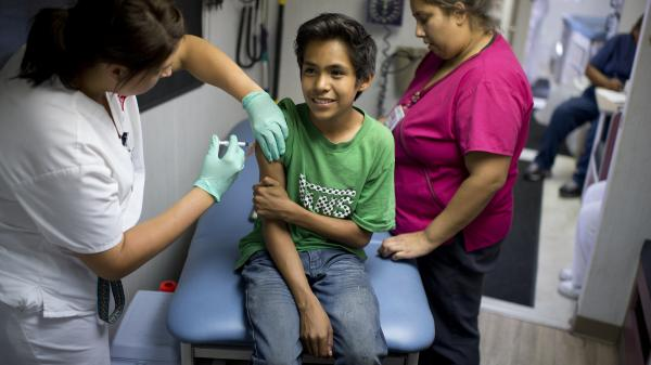 Julio Valenzuela, 11, smiles as he's vaccinated against measles, mumps and rubella at a free clinic in Lynwood, Calif., last August.
