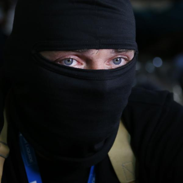A masked pro-Russia gunman looks through a window of a regional administration building seized earlier in Donetsk, Ukraine.