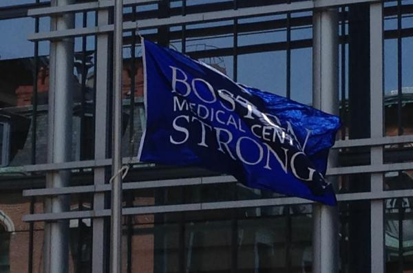 "A flag that says ""Boston Medical Center Strong"" waves outside of Boston Medical Center, a year after the Boston Marathon bombing. (Ron Medzon)"