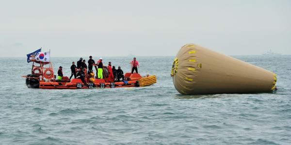 South Korean rescue workers search for missing passengers near the buoy installed to mark a capsized ferry at sea off Jindo on April 18. Divers renewed efforts today to access the capsized ferry.  Of the 400 people who were on board, 200 are still missing. (Jung Yeon-Je/AFP/Getty Images)