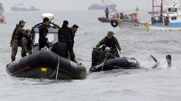 A South Korean navy frogman dives into a water to search passengers believed to have been trapped in the sunken ferry Sewol in the water off the southern coast near Jindo, south of Seoul, South Korea, Saturday.