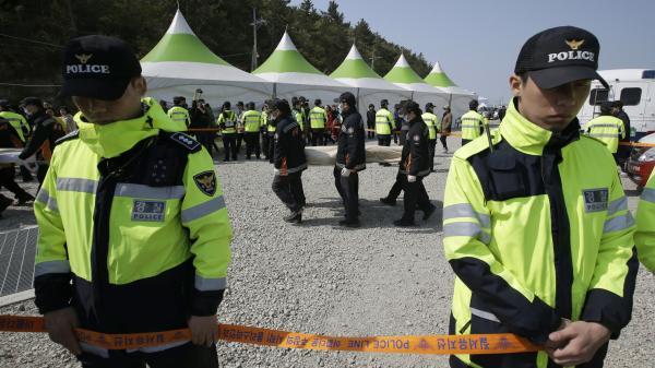 Rescue workers carry the body of a passenger from the ferry that sank Wednesday off the coast of South Korea.
