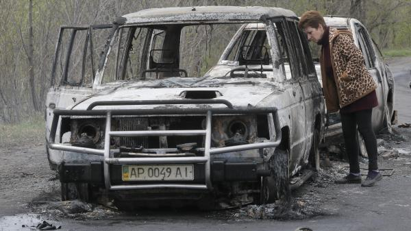 A local resident inspects burnt-out cars after a night gunfight at a checkpoint under control of pro-Russian militants in the village of Bulbasika near Slovyansk Sunday.
