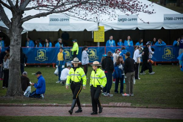 Police officers monitor the area as runners prepare in Boston Common. A year after the terrorist bombings, a far greater security presence is clearly visible.