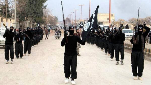 This undated image posted on a militant website in January shows fighters from the al-Qaida linked Islamic State of Iraq and Syria, or ISIS, marching in Raqqa, Syria.