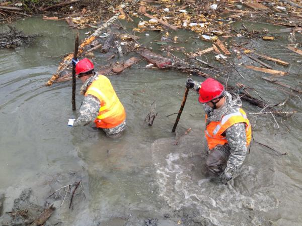 Two members of a search crew look for bodies near the scene of last month's mudslide in Washington state.