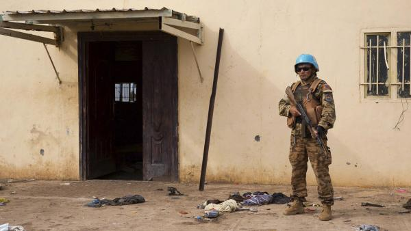 A United Nations peacekeeper stands guard near the scene where about 200 civilians were reported killed during a recent attack in the town of Bentiu.