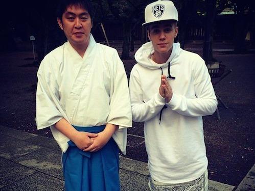 Justin Bieber poses next to an unidentified man at Yasukuni Shrine in Tokyo.