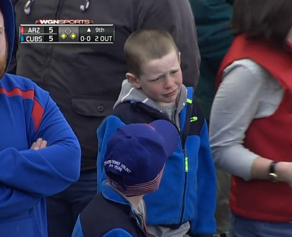 A young fan reacts to the Cubs blowing a lead in the ninth inning.