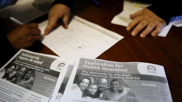 Informational pamphlets are displayed during an enrollment fair on the last day before the sign-up deadline at the Bay Area Rescue Mission in Richmond, Calif.