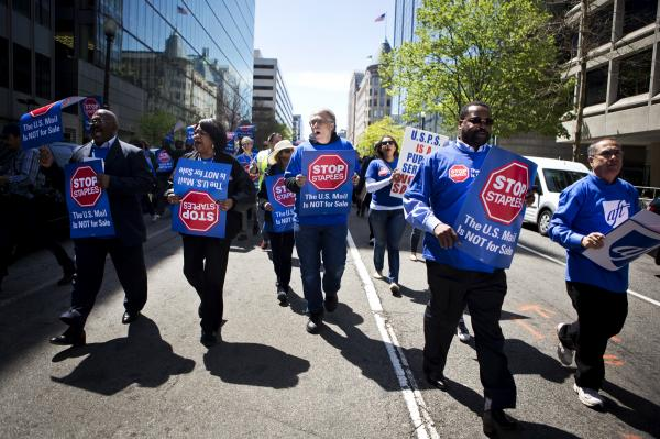 Postal workers take part in a march in Washington, D.C., on Thursday to protest the opening of U.S. Postal Service counters at Staples stores.