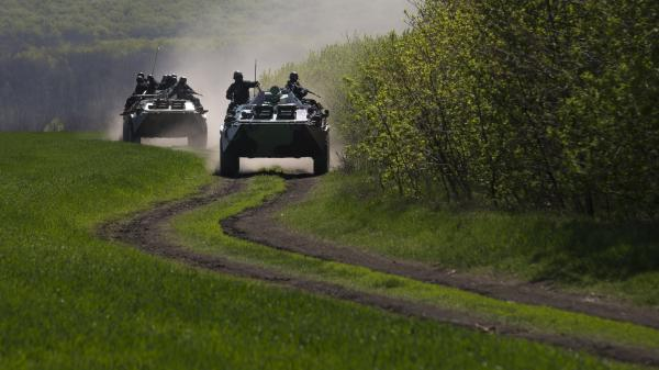 Ukrainian government armored personal carriers roll on a country road outside the town of Svyitohirsk near Slovyansk in eastern Ukraine Saturday.