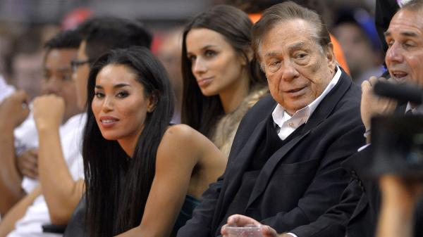 An October 2013 photo shows Los Angeles Clippers owner Donald Sterling, right, and V. Stiviano, left. A recording released Friday includes racist comments allegedly made by Sterling as the couple argued. The NBA is investigating the claim.