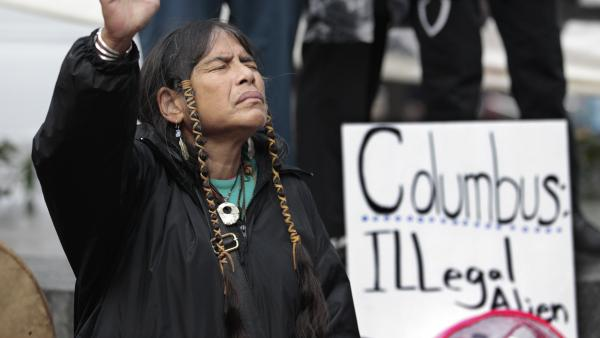 Columbus Day will be designated as Indigenous Peoples Day in Minneapolis, which has become one of several U.S. cities to make the change. Here, a member of the Cowichan Tribes holds her hand up in prayer during a 2011 Native American protest against Columbus Day in Seattle.