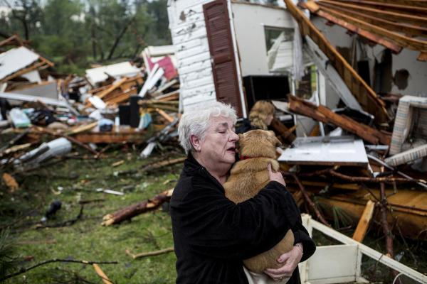 Constance Lambert embraces her dog after finding it alive when she returned to her devastated home in Tupelo. Lambert was away from her home when the tornado struck.