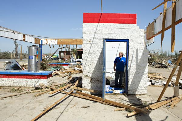 Ken Sullivan, general manager of We Willies Super Auto Wash in Vilonia, looks over the damage after a tornado tore through the area Sunday — the second time in three years.