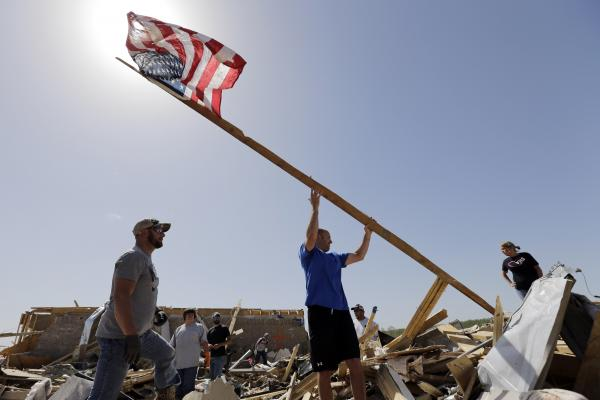 Justin Shaw (left) helps Nick Conway erect a flagpole at what had been his Vilonia home.