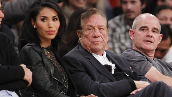 Los Angeles Clippers owner Donald Sterling (center) has been banned by the NBA; he is seen here watching a Clippers game with former girlfriend V. Stiviano.